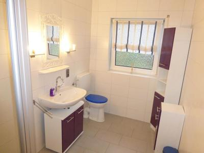 Badezimmer mit Fenster, ebenerdiger Dusche, und WC