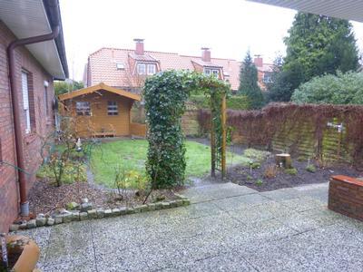 Blick durch den Garten vom Ferienhaus Renate mit Terrasse und Blockhütte. Gartenmöbel sind vorhand