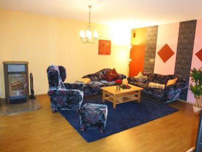 Großes Wohnzimmer mit Kamin, Flachbildfernseher (Sat-TV) und gemütlichen Sofas.