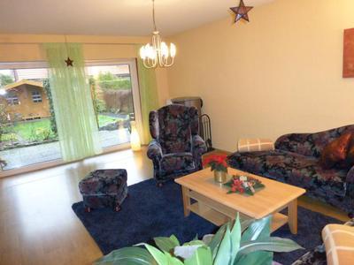 Großes Wohnzimmer mit gemütlicher Sitzecke und Zugang zur Terrasse mit Garten