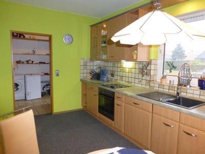 Gut ausgestattete Küche mit Blick in den Abstellraum mit Waschmaschine, Mikrowelle, etc.