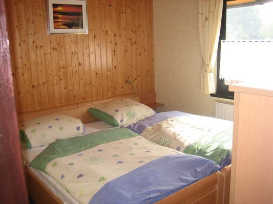 Schlafzimmer mit Doppelbett und zweitem TV